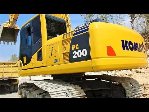 Komatsu PC200-8 Excavator Loading Limestone Into Dump Truck On Road Construction Site